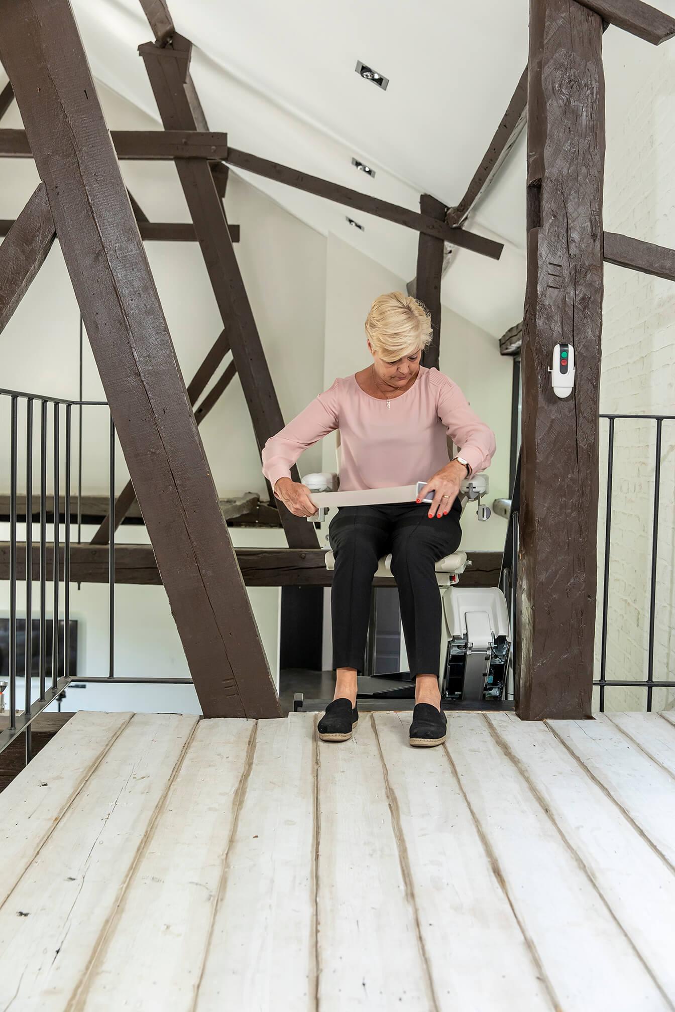 Femme qui s'installe dans un siège monte-escalier