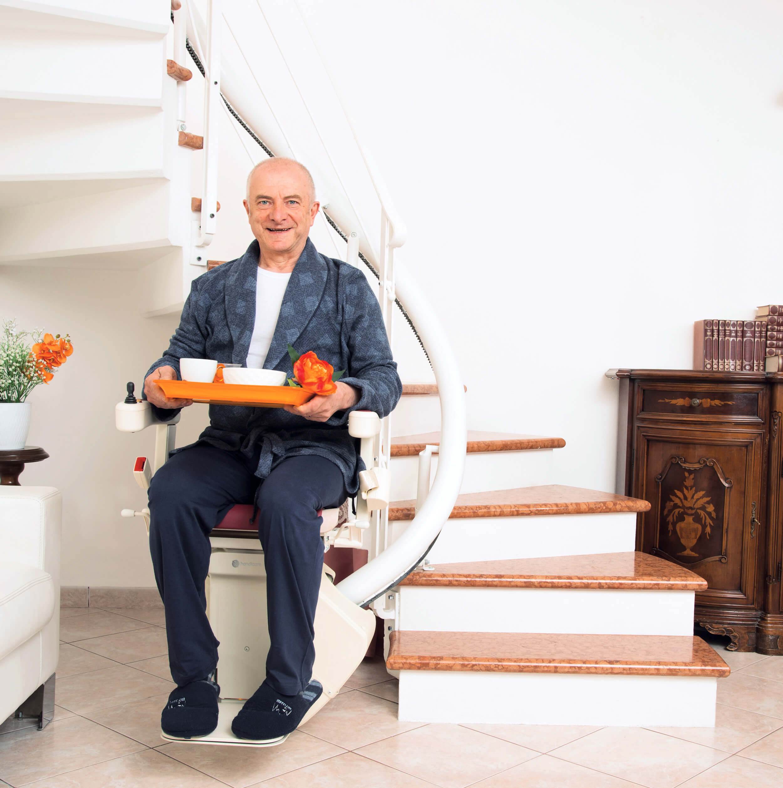 Homme assis sur un fauteuil monte-escalier avec un plateau repas à la main